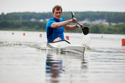Young kayaker paddling during competition on the lake