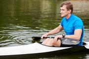 Kayaking man at the kayak boat getting leisure on the lake