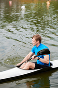 Young sportsman kayaking on lake in boat, he is competing in summer watersport