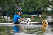 Sporty man is kayaking  on the river during rowing competition