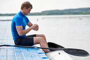 Young athlete sitting on pier and waiting for rowing competition