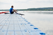 Young kayaker sitting on the pier with kayak and paddle and waiting for rowing competition