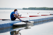 Young sportsman sitting and resting on pier after rowing competition