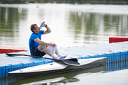 Young sportsman sitting on pier and drinking water from bottle, he resting after rowing training