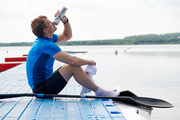 Young athlete resting on pier near the lake and drinking water after rowing competition