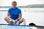 Portrait of young kayaker sitting on pier with bottle of water, he is resting after training