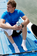 Young athletic man resting on pier after training and thinking about future competition