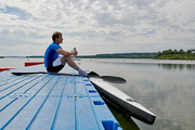 Side view of young athlete resting on pier and drinking water after rowing training