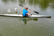 Young athletic kayaker taking part in rowing competition on the lake