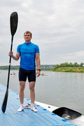 Portrait of young sportsman holding scull while standing on pier and his kayak in water and he is ready for rowing competition