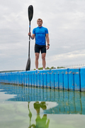 Young sportsman in sportswear standing on pier with paddle, he is ready for kayaking