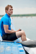 Young kayaker in sportswear sitting on pier and listening to music on mobile phone or has a conversation on the phone