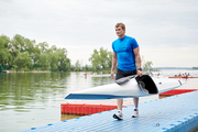 Young man in sportswear walking along the pier with his kayak, he finished his training on the lake