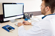 Portrait of mature doctor using PC sitting at desk in office and typing work notes looking at blank white screen