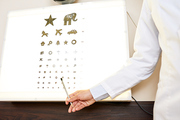 Close up of  ophthalmologist hand pointing to eye chart for children  with pictures on it in pediatric optometry office, copy space