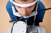 High angle close up of young man  looking at slit lamp machine, resting head on stand during sight testing in optometrist office