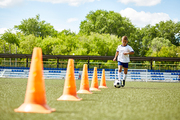 Portrait of boy in uniform leading ball between cones during  practice in field on sunny day