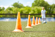 Blurred figure of teenage boy doing exercises during football practice, ready to lead ball between orange cones, focus on foreground