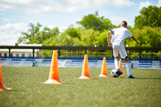Back view portrait of teenage boy running in football field leading ball between row of orange cones during practice