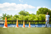 Blurred figure of teenage boy standing by row of orange cones, focus on foreground