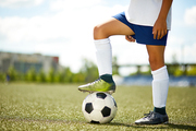 Side view portrait of unrecognizable young sportsman standing in football field with leg on ball