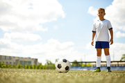 Portrait of smiling boy wearing uniform standing in football field next to ball, focus on foreground
