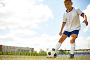 Portrait of  teenage boy running in field to kick the ball during football practice, copy space