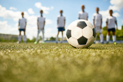 Closeup of football ball on green grass with blurred shapes of junior football team in background