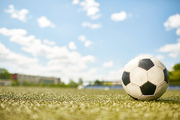 Closeup of ball lying on green grass in empty football field, copy space