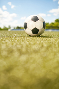 Closeup of ball lying on green grass in empty football field
