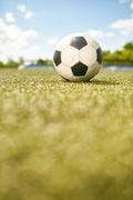 Closeup of ball lying on green grass in empty football field