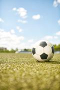 Closeup of ball lying on green grass in empty football field in sunlight