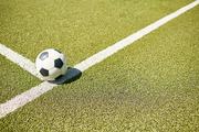 High angle closeup of ball lying on green football field, copy space