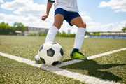 Closeup portrait of unrecognizable teenage boy kicking ball during football practice in field outdoors
