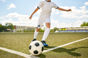 Portrait of unrecognizable teenage boy kicking ball during football practice in field outdoors