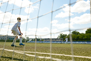 Back view portrait of teenage goalkeeper protecting gate during junior football tem  practice, shot from behind gate net