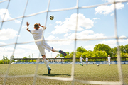 Back view portrait of teenage goalkeeper jumping to catch ball during junior football match or practice, shot from behind gate net