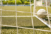 Closeup image of ball in gate on football field, shot from behind the net