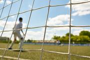 Back view portrait of teenage goalkeeper standing in gate during match between junior football teams, shot from behind gate net