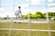 Back view portrait of teenage goalkeeper protecting gate during junior football match shot from behind gate net