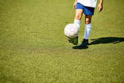 Low section portrait of unrecognizable young sportsman playing with ball  in football field outdoors