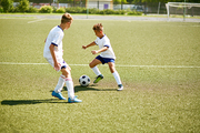 Portrait of two boys playing football during junior team practice in field