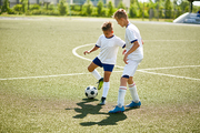 Portrait of two teenage boys playing football during junior team practice in field