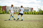 Portrait of two teenage boys playing football during outdoor junior team practice in field