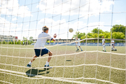 Back view portrait of teenage goalkeeper catching ball during match between junior football teams, shot from behind gate net