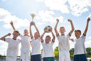 Portrait of happy boys in junior football team standing in row holding champions cup and cheering after winning match
