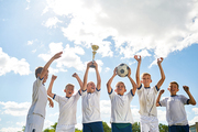 Portrait of happy boys in junior football team standing in row holding trophy cup and cheering after winning match