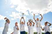 Portrait of boys in junior football team cheering happily and jumping holding trophy after winning match