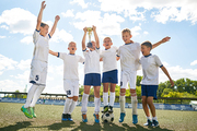 Portrait of junior football team cheering happily and jumping holding trophy cup after winning match