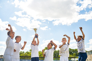 Portrait of boys in junior football team cheering happily and jumping holding trophy cup after winning match